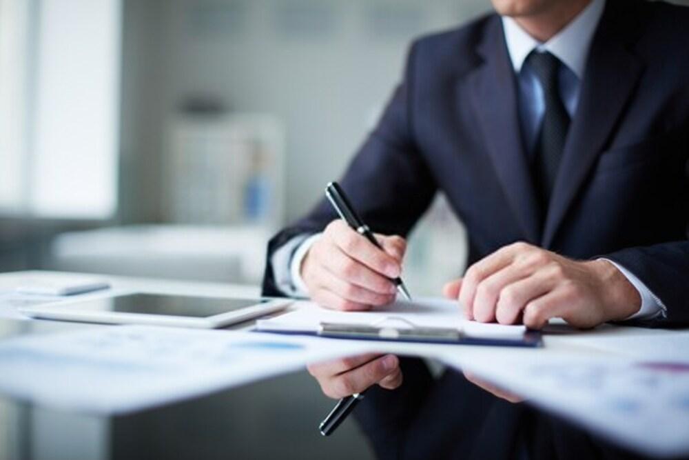 mezczyzna podpisujacy dokumenty